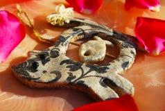 Kall souvenirkatt med en pilbåge på en rad i kronbladen av rosor Arkivbild