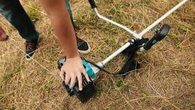Kall start av en bensingräsmattabeskärare Händer av en yrkesmässig gräsklippare arkivfilmer