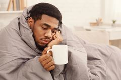 Kall svart man med influensa som slås in i varm filt royaltyfri bild