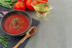 Kall tomatgazpachosoppa i en djup platta p? en stenbakgrund royaltyfri foto