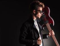 Kall ung gitarrist som rymmer hans elektriska gitarr på skuldra Arkivbild