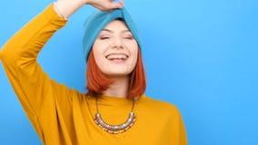 Kall ung kvinna som bär en blå hatt och spelar med den arkivfilmer