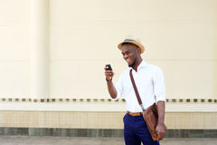 Kall ung svart man som ser mobiltelefonen Royaltyfria Bilder