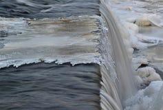 Kall vinterflod - iskall vattenfall vid den långsamma slutaren Arkivfoto