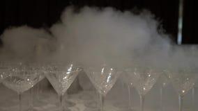 Kall vit rökspridning längs en rad på tabellen, tomt Martini exponeringsglas Lämna kameran från ett stort antal stock video