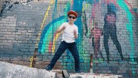 Kalla 5 åriga danser för ett barn i solglasögon nära en tegelstenvägg med grafitti, en ung gatadansare, stock video