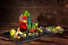 Kalla coctailar med mintkaramellen, limefrukt, bär och carambolaen på det svarta skrivbordet Ljusa sommardrycker alkoholiserada d Royaltyfria Foton