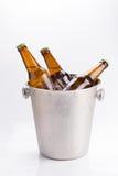 kalla flaskor av öl i hink med is på vit bakgrund arkivfoto