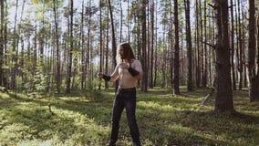 Kalla grabbdrev i trämeleen med en kniv i hans händer Kyla kastar en kniv från handen för att räcka stock video