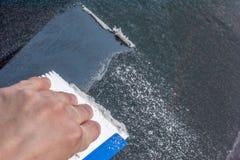 Kalla händer som skrapar bilfönstret arkivbilder