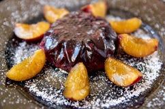Kalla lilor göra gelé av med nya frukter och pulver som dekoreras med plommoner på den mörka plattan på svart träbakgrundsslut up Royaltyfria Bilder