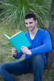 Kalla män för barn i parkera som läser en bok Arkivbild