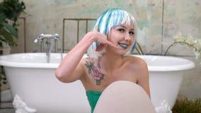 Kalla mig gesten av den härliga flickan i peruk i badrummet lager videofilmer
