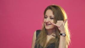 Kalla mig gesten av den härliga flickan, rosa bakgrund i studio arkivfilmer