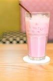 Kalla rosa färger mjölkar i exponeringsglas på den wood tabellen Royaltyfri Bild