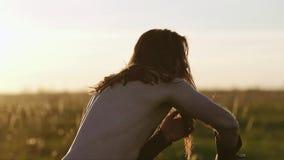 Kalla vikingkrigaredrev med en kniv i fältet mot en härlig solnedgång Bedöva strålar av solen En man slår på en imag lager videofilmer