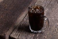 Kallade den lokala drycken för det thailändska med is häftet för svart kaffe på träbakgrund oliang Arkivfoto