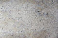 Kallade den naturliga ljusa beigea stenen för bakgrund med mörka stänk granit Bianco Romano arkivfoto