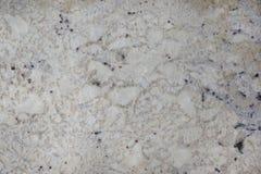 Kallade naturlig stenbeiga för bakgrund med mörka fläckar granit Bianco Romano arkivbild