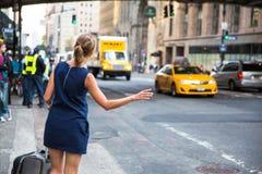 Kallande/hailking taxitaxi för flicka på Manhattan Royaltyfri Foto