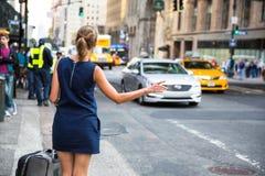 Kallande/hailking taxitaxi för flicka på Manhattan Arkivfoto