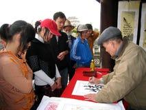 Kalligrafen die de kunstbrieven schrijven Stock Afbeeldingen