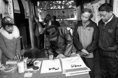 Kalligrafer som skrivar konstbrev för besökare Fotografering för Bildbyråer