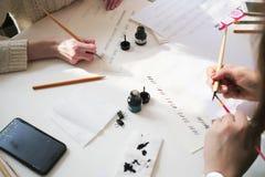 Kalligrafibokstäverseminarium Foto av handen för ` s för två unga kvinnor Royaltyfri Fotografi