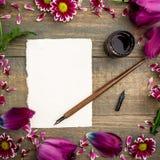 Kalligrafiedocument kaart met bloemen, inktpen op witte achtergrond Vlak leg, hoogste mening Royalty-vrije Stock Foto's