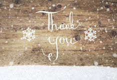 Kalligraphie danken Ihnen, rustikalem hölzernem Hintergrund, Schnee, Schneeflocken Stockfotos