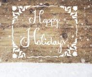 Kalligraphie frohe Feiertage, hölzerner Hintergrund, Schnee, Schneeflocken Stockbild