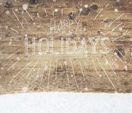Kalligraphie frohe Feiertage, Schnee, hölzerner Hintergrund, Schneeflocken Lizenzfreies Stockbild