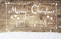 Kalligraphie-frohe Weihnachten und guten Rutsch ins Neue Jahr, hölzerner Hintergrund, Schneeflocken Lizenzfreie Stockbilder