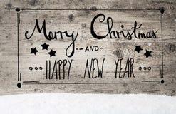 Kalligraphie-frohe Weihnachten und guten Rutsch ins Neue Jahr, Weinlese-Hintergrund, Schnee Stockfotos