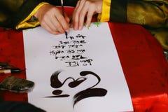kalligraphie schreibkünstler calligraphic Tet-Feiertage Tet-Vorabend lizenzfreie stockfotografie