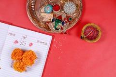 Kalligraphieschreiben in hindi Shubha Labh bedeutet Güte u. Reichtum, über rotem erklärendem Anmerkungsbuch, diya, stockfotos