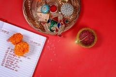 Kalligraphieschreiben in hindi Shubha Labh bedeutet Güte u. Reichtum, über rotem erklärendem Anmerkungsbuch, diya, lizenzfreies stockbild