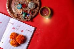 Kalligraphieschreiben in hindi Shubha Labh bedeutet Güte u. Reichtum, über rotem erklärendem Anmerkungsbuch, diya, lizenzfreies stockfoto