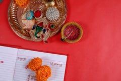 Kalligraphieschreiben in hindi Shubha Labh bedeutet Güte u. Reichtum, über rotem erklärendem Anmerkungsbuch, diya, lizenzfreie stockfotografie