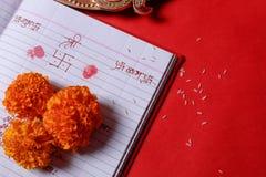 Kalligraphieschreiben in hindi Shubha Labh bedeutet Güte u. Reichtum, über rotem erklärendem Anmerkungsbuch, diya, lizenzfreie stockbilder