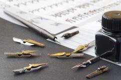 Kalligraphiestifttipps, Ebene spitzten Spitze, Tinte und Praxisblätter auf dem Tisch Lizenzfreies Stockbild