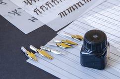 Kalligraphiestifttipps, Ebene spitzten Spitze, Tinte und Praxisblätter auf dem Tisch Stockfotografie