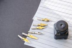 Kalligraphiestifttipps, Ebene spitzten Spitze, Tinte und Praxisblätter auf dem Tisch Lizenzfreie Stockbilder