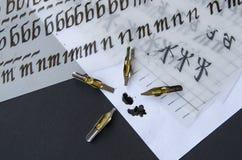 Kalligraphiestifttipps, Ebene spitzten Spitze, Tintenflecke und Praxisblätter auf dem Tisch Lizenzfreie Stockfotografie
