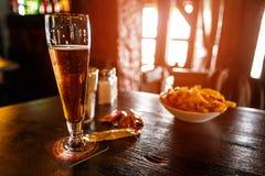 Kallt öl i ett exponeringsglas på en trätabell i baren royaltyfri fotografi