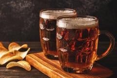 Kallt öl i exponeringsglas med chiper på en mörk bakgrund arkivbild