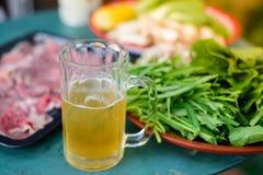 Kallt öl i exponeringsglaset och råvarorna för att laga mat arkivfoto