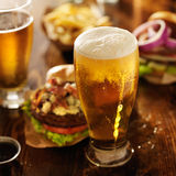 Kallt öl med det skummande huvudet och hamburgare royaltyfria foton