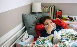 Kallt barn som ligger på sängen arkivbild