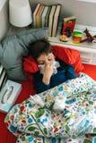 Kallt barn som ligger på sängen royaltyfri bild